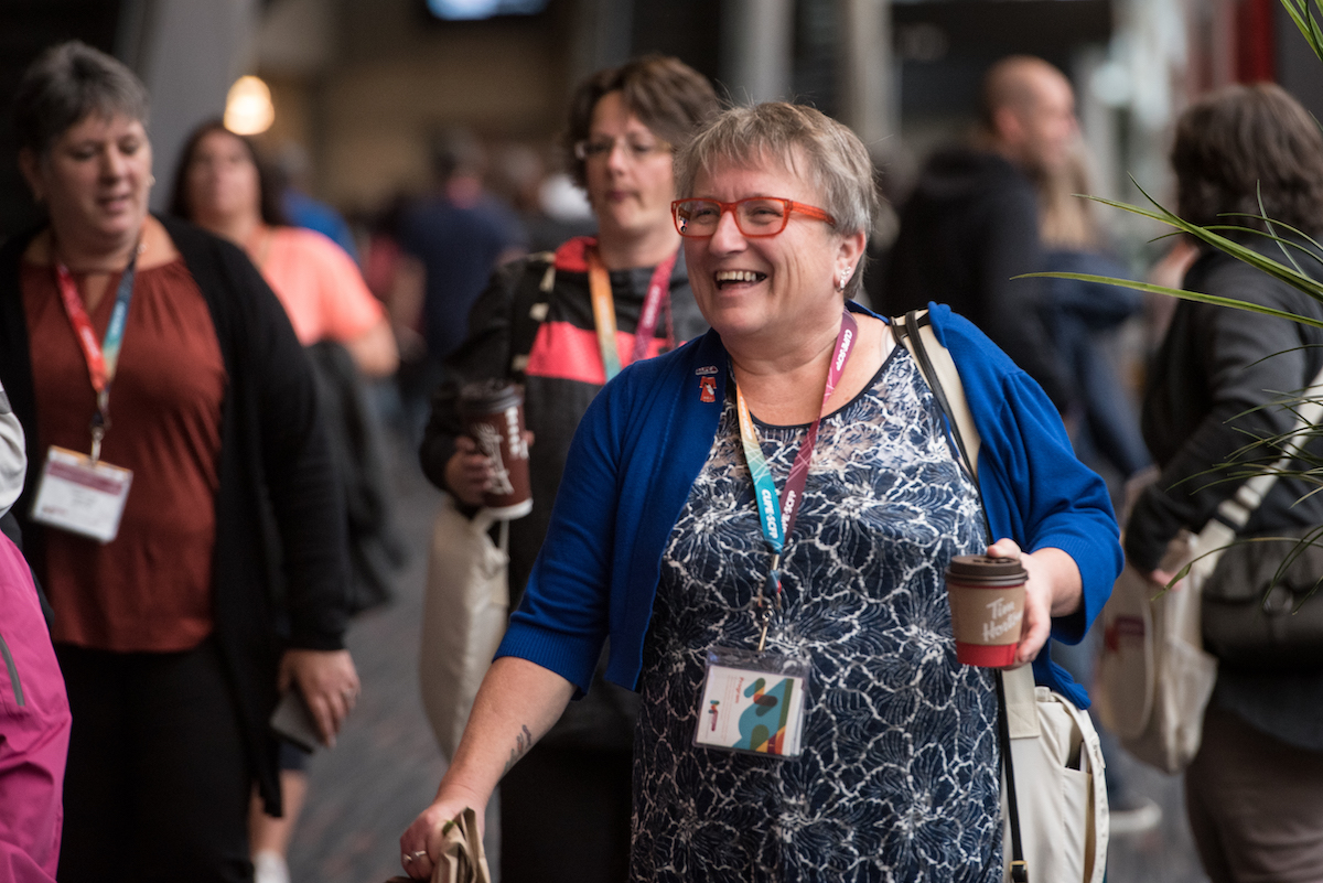 Photo of Nan McFadgen walking through crowd in a corridor at CUPE National Convention in 2019.